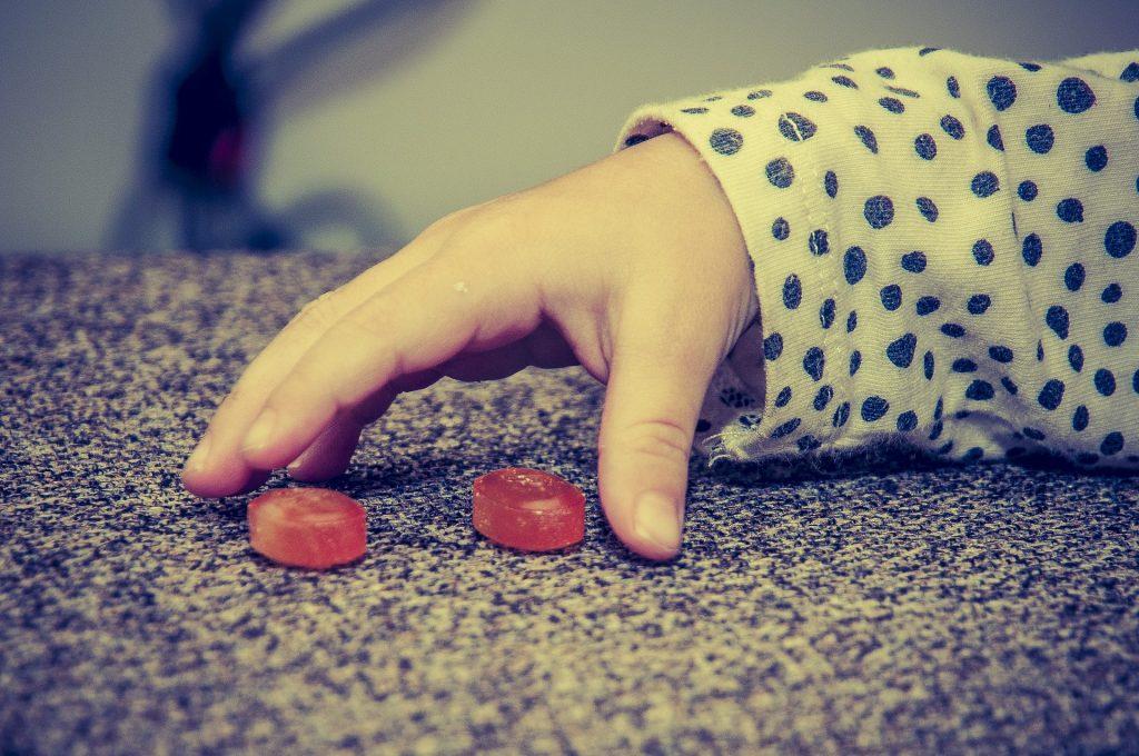 main d'enfant prenant deux bonbons